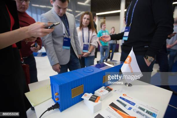 Visitors inspect a demonstration model of a shipping container industrial mining farm at the Bitferma promotional stand at the CrytoSpace conference...