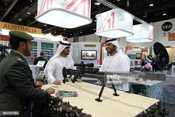 Visitors inspect a Steyr Mannlicher HS50 127 long range rifle with a Kahles scope at the International Defence Exhibition in Abu Dhabi United Arab...