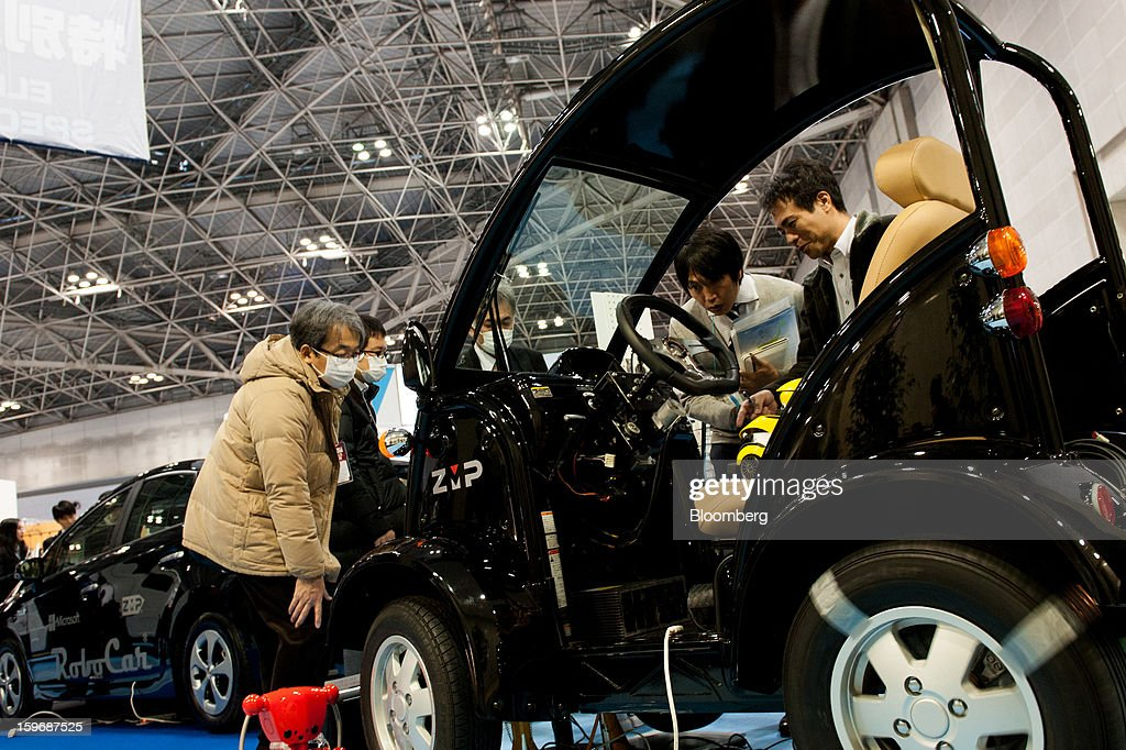 Visitors inspect a ZMP Inc. Car Robotics Platform Robocar MV2 vehicle at Automotive World 2013 in Tokyo, Japan, on Friday, Jan. 18, 2013. The Automotive World 2013 trade show ends today. Photographer: Noriko Hayashi/Bloomberg via Getty Images