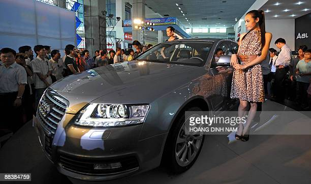 Visitors inspect German carmaker Audi's A6 sedan on display at Vietnam Autoexpo 2009 in Hanoi on June 10 2009 Despite the absence of a local...