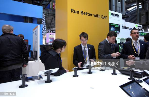 Visitors inspect mobile handsets and tablet devices on display inside the SAP AG pavilion at the Mobile World Congress in Barcelona Spain on Tuesday...