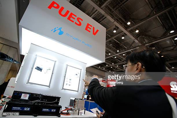 Visitors inspect Pues Corp 552V lithiumion battery packs equipped with Toshiba Corp's SCiB battery cell modules left at Automotive World 2014 in...