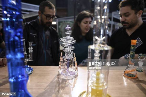 Visitors inspect the designs of marijuana smoking apparatus also known as 'bongs' at the 1st International Cannabis Expo at the Faliro Sports...