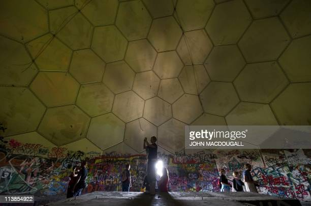 Visitors inspect the main radar dome of a former US National Security Agency run listening station on top of the Teufelsberg in western Berlin's...