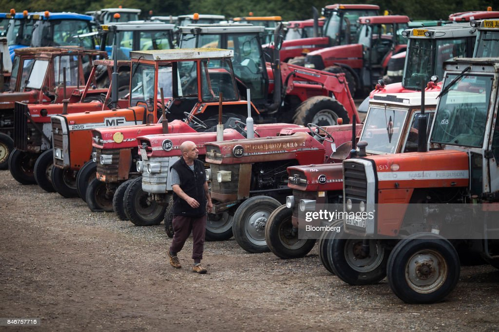 A visitors inspects tractors, manufactured by Massey Ferguson Corp., before they are put up for auction at the Cheffins Cambridge Machinery Sales monthly machinery and plant auction in Sutton, U.K., on Monday, Sept. 4, 2017. The debate over food andfarmingpolicy after Brexit has heated up recently, with Environment Secretary Michael Gove telling BBC Radio 4 that the U.K wouldnt lower its animal welfare or environmental standards to achieve any new trade deals. Photographer: Simon Dawson/Bloomberg via Getty Images