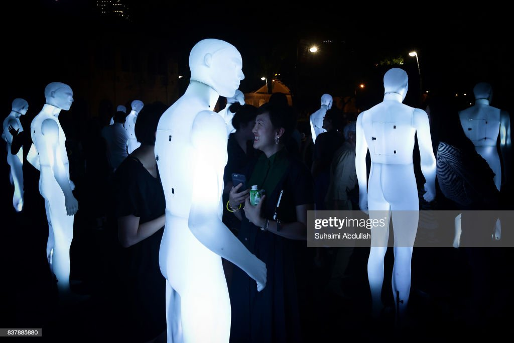 Visitors interact with an art installation of human sized figurines, 'The Standing Men' by AADN of France during the Singapore Night Festival media preview on August 23, 2017 in Singapore.