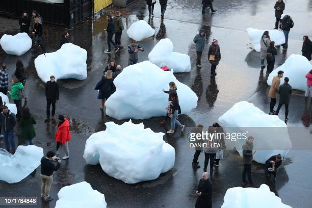 Visitors interact with blocks of melting ice an exhibit entitled 'Ice Watch' created by IcelandicDanish artist artist Olafur Eliasson and leading...