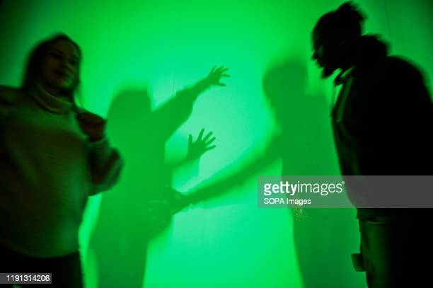 Visitors interacts with infra red lights illusions at the Museum of illusions in Krakow The Museum of Illusions bring a collection of holograms and...