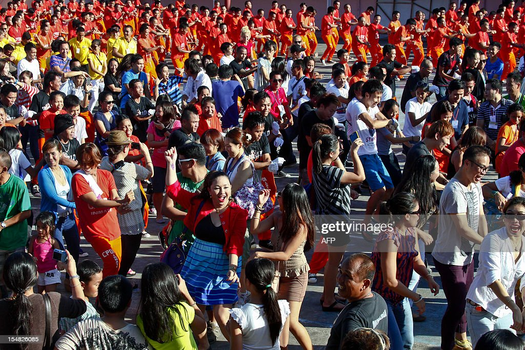 Visitors join inmates (orange uniforms) to dance to the tune of the horse-riding dance made famous by South Korean rapper Psy at the Provincial Detention and Rehabilitation Center in Cebu on October 27, 2012. Philippine convicts who became famous for dancing to Michael Jackson's hits have added South Korean spice to their repertoire, with a performance of the popular 'Gangnam Style' rap.