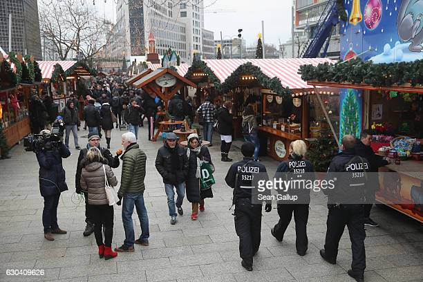 Visitors journalists and police walk through the reopened Breitscheidplatz Christmas market only a short distance from where three days ago a truck...