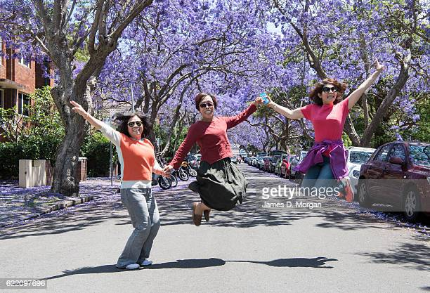 Visitors jump for a photograph on McDougall Street in the north Sydney suburb of Kirribilli on November 10 2016 in Sydney Australia Jacaranda trees...