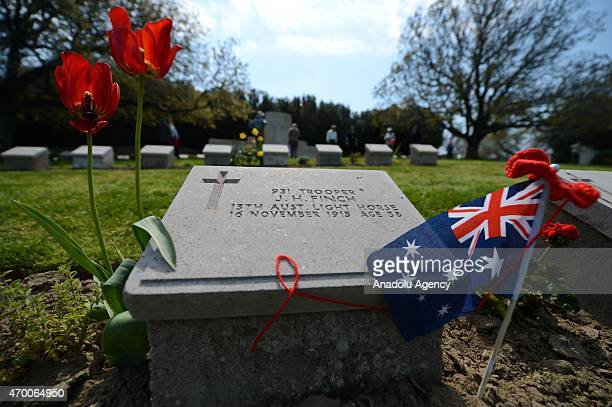 Visitors lay flowers to the headstones of Australian soldiers killed during the Canakkale Land Battles lie at a cemetery at Anzac Cove in Canakkale...