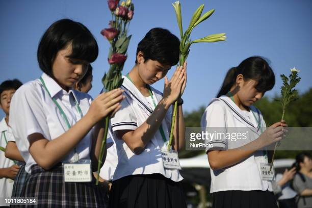 Visitors lays flowers and pray for the atomic bomb victims in front of the cenotaph at the Hiroshima Peace Memorial Park in Hiroshima Western Japan...