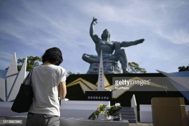 Visitors lays flowers and pray for the atomic bomb victims in front of the Nagasaki Peace Park in Nagasaki southern Japan August 9 2018 Japan marks...