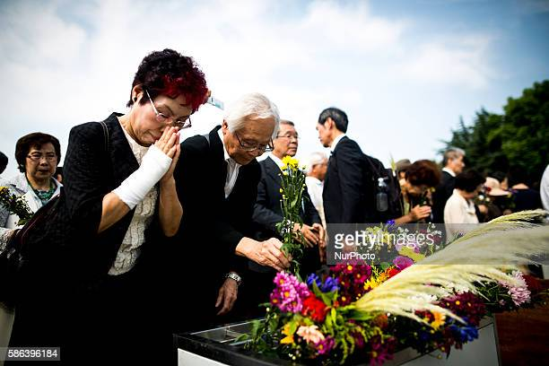 Visitors lays flowers and pray for the atomic bomb victims in front of the cenotaph during the 71st anniversary of the atomic bombing on Hiroshima at...