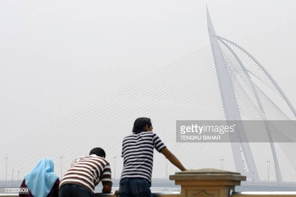 Visitors lean on a ledge while the landmark Seri Wawasan bridge is seen through thick haze in Putrajaya 18 October 2006 Air quality in Malaysia's...