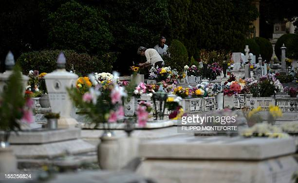 Visitors leave flowers in front of a grave at Rome's Verano monumental cemetery on November 2 2012 for all Souls Day All Souls Day is a solemn feast...