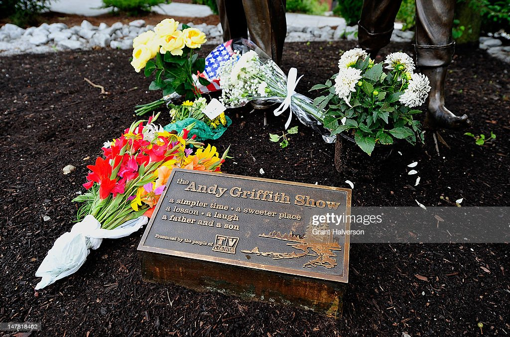 Visitors leave flowers next to a statue outside of the Andy Griffith Museum in remembrance of actor Andy Griffith on July 3, 2012 in Mt Airy, North Carolina. Griffith died around 7am at his North Carolina home at age 86.