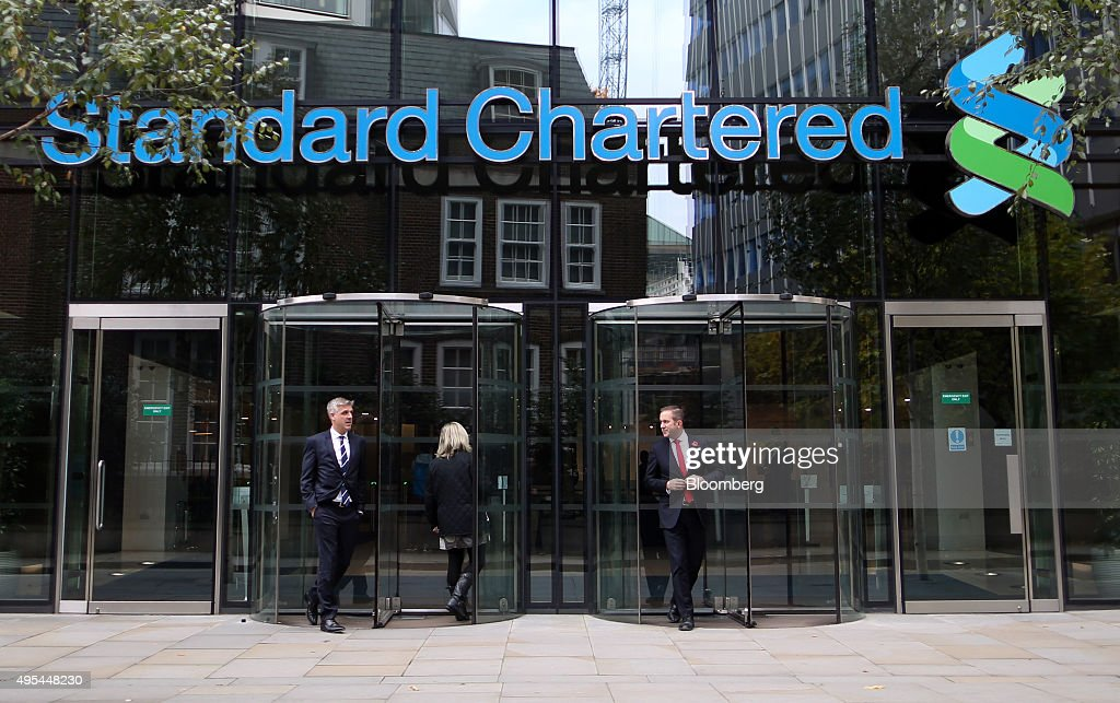 Visitors leave the headquarters of Standard Chartered Plc in London, U.K. on Tuesday, Nov. 3, 2015. Standard Chartered Plc dropped the most in more than three years after the lender said it plans to eliminate 17 percent of its workforce, scrap the dividend and tap investors for $5.1 billion as Chief Executive Officer Bill Winters seeks to restore profit growth. Photographer: Chris Ratcliffe/Bloomberg via Getty Images
