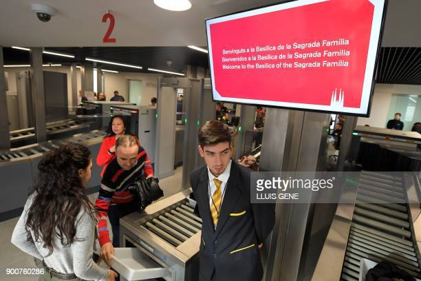Visitors leave their belongings to walk through security screening before accessing the Sagrada Famila Basilica in Barcelona, on January 3, 2018. The...