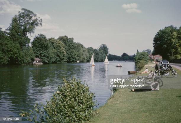 Visitors lie on the grass banks of the River Thames near the village of Pangbourne in Berkshire, England circa 1960.