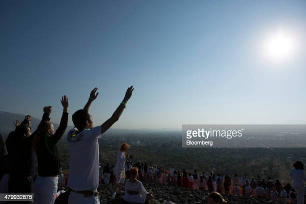 Visitors lift their hands toward the sun at the top of the Pyramid of the Sun during celebrations for the Spring Equinox at the archaeological site...