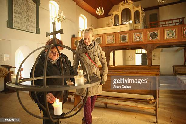 Visitors light a candle in the village church during a protest being held outside against the expansion of openpit lignite coal mines at the annual...