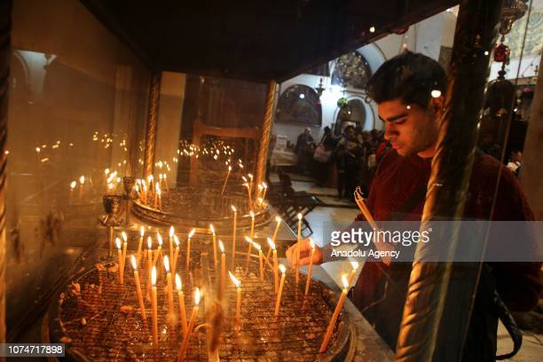 Visitors light candles at the Church of the Nativity at the Church of the Nativity during Christmas ceremony in Bethlehem West Bank on December 23...