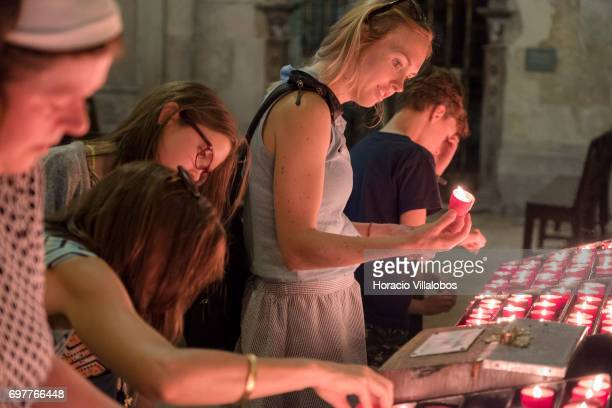 Visitors light candles at the Se de Lisboa the city's cathedral on June 18 2017 in Lisbon Portugal Although active all year round Portuguese tourist...