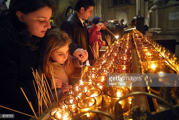 Visitors light candles in St Patrick's Cathedral a favorite Christmas spot for tourists December 4 2001 in New York City New York is in full holiday...