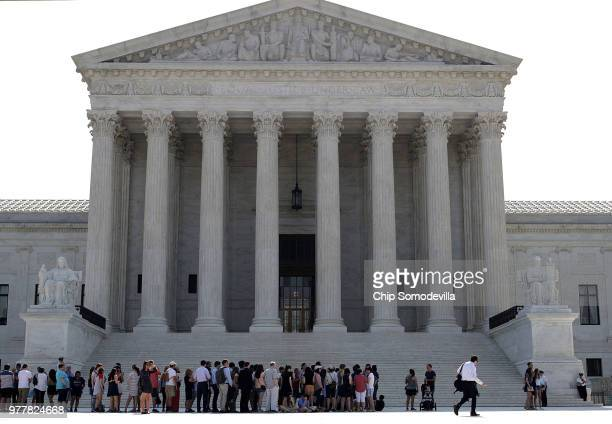 Visitors line up outside the US Supreme Court plaza before the court handed down decisions June 18 2018 in Washington DC The court handed down...
