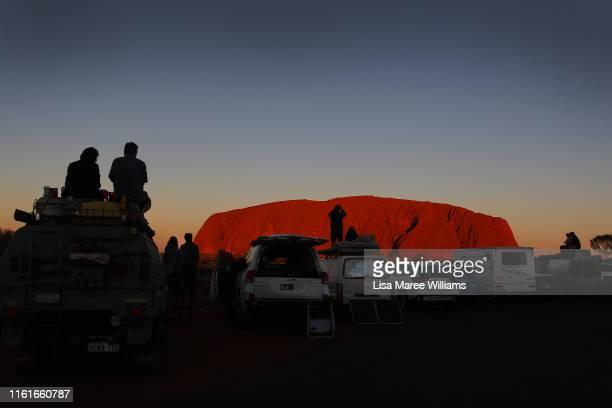 Visitors line up their vehicles to take in the sunset view of Uluru on August 12 2019 in the UluruKata Tjuta National Park Australia The UluruKata...