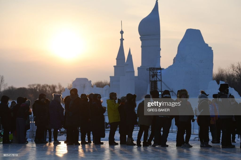 Visitors line up to climb a snow sculpture before the opening of the annual Harbin Ice and Snow Sculpture Festival in Harbin in China's northeast Heilongjiang province on January 5, 2018. The festival attracts hundreds of thousands of visitors annually. / AFP PHOTO / Greg Baker