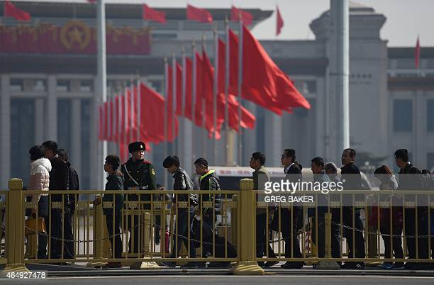Visitors line up to enter Tiananmen Square next to the Great Hall of the People the venue for upcoming meetings of China's legislature in Beijing on...