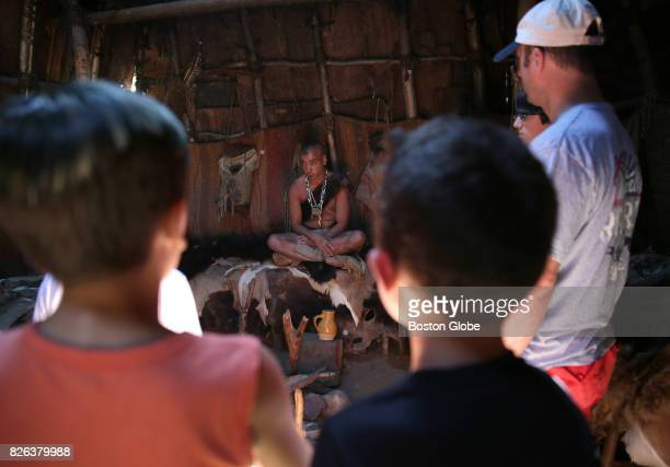 Visitors listen to Costumed Role Player Tim Turner at the Wampanoag Homesite at Plimoth Plantation in Plymouth MA on Jul 26 2017