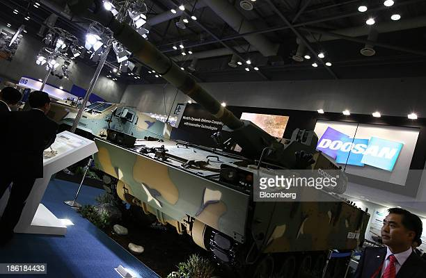 Visitors look a model of a Doosan DST Co. Medium tank at the Seoul International Aerospace & Defense Exhibition 2013 in Goyang, South Korea, on...