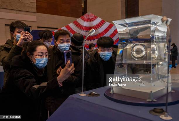 Visitors look and take pictures of a case holding lunar rock and debris recently collected from the Moon by China's space program that is part of a...