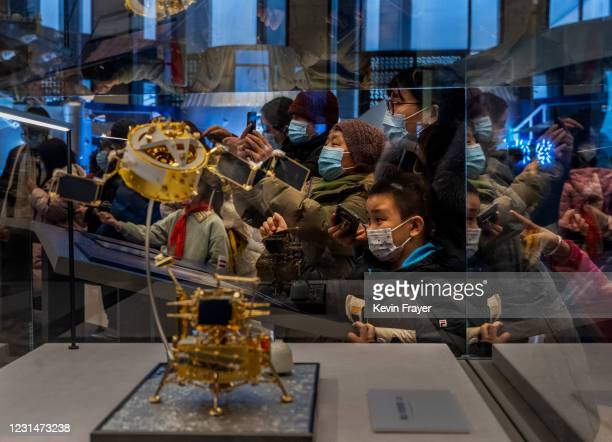 Visitors look and take pictures of equipment from China's space program that is part of a display at the National Museum of China on March 2, 2021 in...
