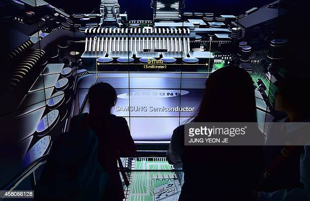 Visitors look around a Samsung Electronics showroom at their headquarters in Seoul on October 30 2014 Samsung reported a near 50 percent fall in...