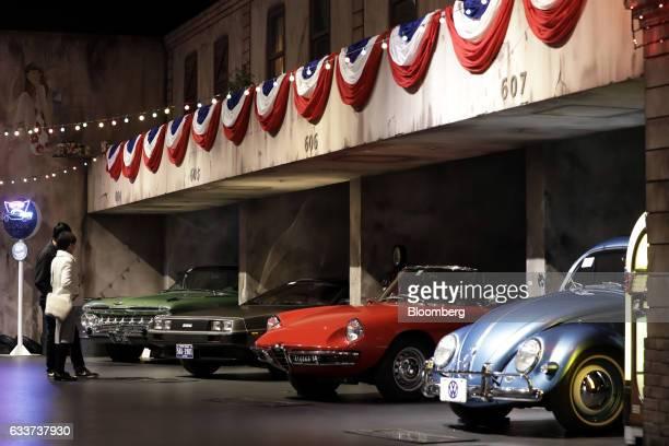 Visitors look at a 1959 General Motors Co Chevrolet Impala vehicle from second left a 1981 Delorean DMC12 vehicle a 1966 Alfa Romeo Inc 1600 Spider...