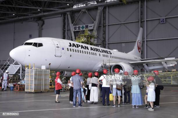 Visitors look at a Boeing Co 737 aircraft operated by Japan Airlines Co at JAL's hangar during a tour at Haneda Airport in Tokyo Japan on Wednesday...