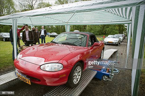 Visitors look at a cabrio in Maarssen on May 2010 About 740 Mazda MX5 cabrios gathered at the Maarsseveense Plassen to celebrate the 20th anniversary...