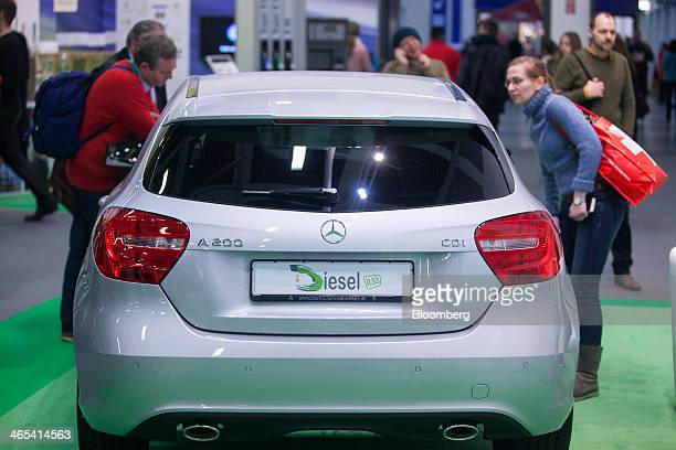 Visitors look at a Daimler AG MercedesBenz AClass automobile as it stands on the Neste Oil Oyj biofuel diesel trade stand at the Green Week...