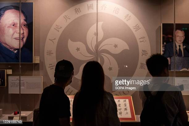 Visitors look at a display featuring a portrait of former Chinese leader Deng Xiaoping, , and Hong Kongs first Chief Executive Tung Chee-hwa, , at...