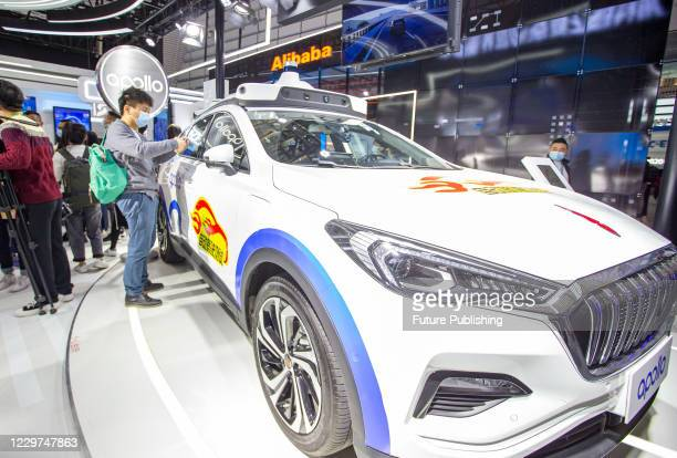 """Visitors look at a display of a self-driving test car at the Baidu booth at the """"Light of the Internet"""" Expo at the World Internet Conference 2020 in..."""