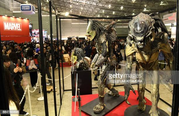 """Visitors look at a display of Predalien figures from the 2007 film """"Aliens vs. Predator: Requiem"""" at Tokyo Comic Con 2017 at Makuhari Messe in Chiba..."""