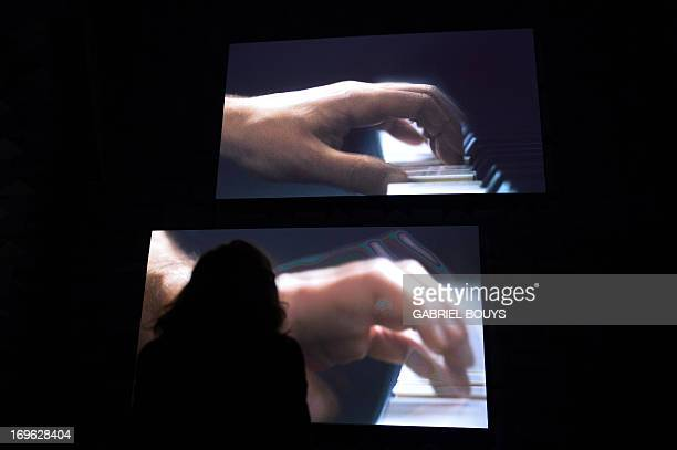 Visitors look at a film by Anri Sala's Ravel Ravel Unravel installation at the French pavilion during the press preview of the 55th Venice art...