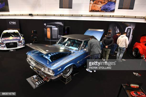 Visitors look at a Ford Galaxie classic car on December 1 2017 during the 'Essen Motor Show' fair in Essen western Germany According to the...