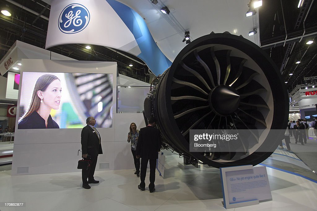 Visitors look at a General Electric Co. GEnx aircraft engine displayed on the company's stand on the first day of the Paris Air Show in Paris, France, on Monday, June 17, 2013. The 50th International Paris Air Show is the world's largest aviation and space industry show, and takes place at Le Bourget airport June 17-23. Photographer: Balint Porneczi/Bloomberg via Getty Images