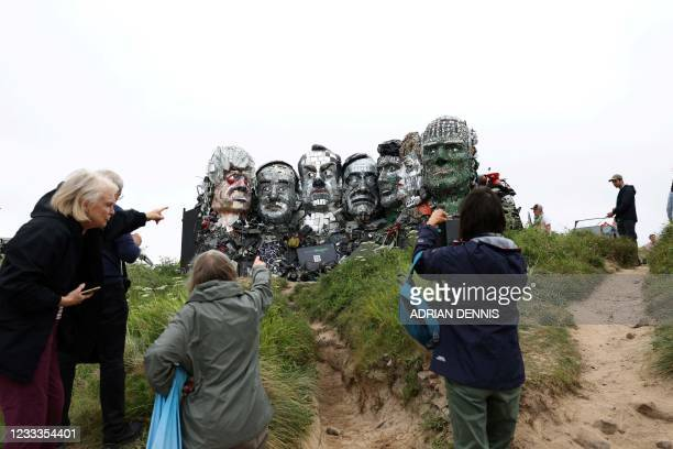 Visitors look at a giant Mount Rushmore-style sculpture of the G7 leaders heads, made entirely of discarded electronics, is displayed on a beach near...